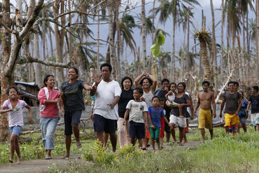 Typhoon Haiyan survivors smile as they walk from a village on Leyte (Reuters)
