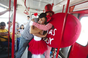 Performers hug a passenger on Lima's electric train during Valentine's Day (Reuters)