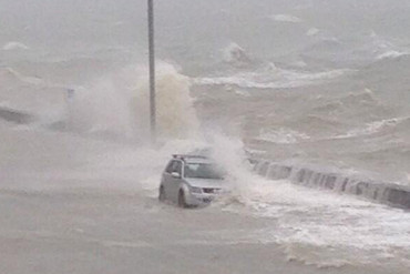 A car is lashed by waves on Tamaki Drive (Photo: @FromAQuasar)