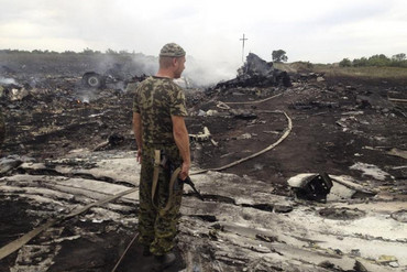 An armed pro-Russian separatist stands at a site of a Malaysia Airlines